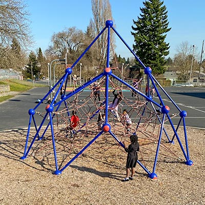 Photo of a play area with a net climber and rock wall.