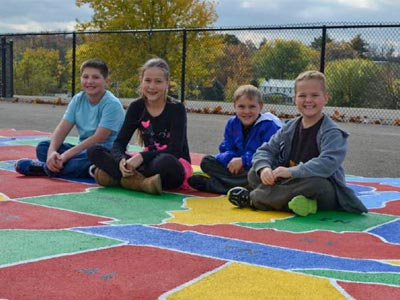 Children sitting on a playground surface painted with a map of the United States.