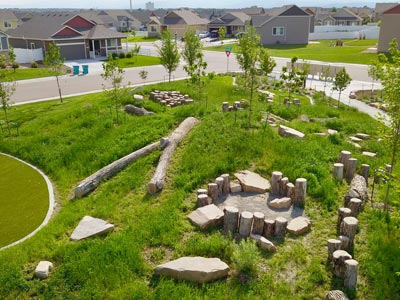 A play area featuring logs and boulders.