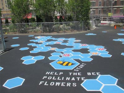 A bee-themed painting on a playground surface.