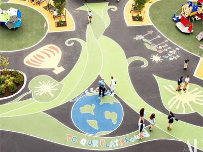 A play area featuring a nature-themed painting on playground surface, with adjacent planted areas.