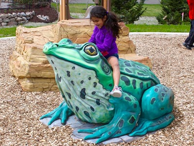 A child playing on a frog sculpture.