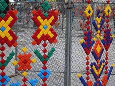 A chain-link fence decorated with brightly-colored patterns.