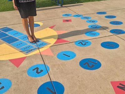 A playground surface painted with a sundial.