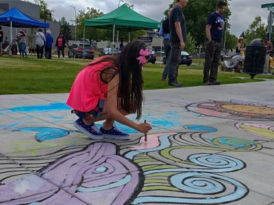 A student painting on a playground surface.