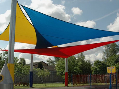 A playground structure holding brightly-colored sails that create shade.